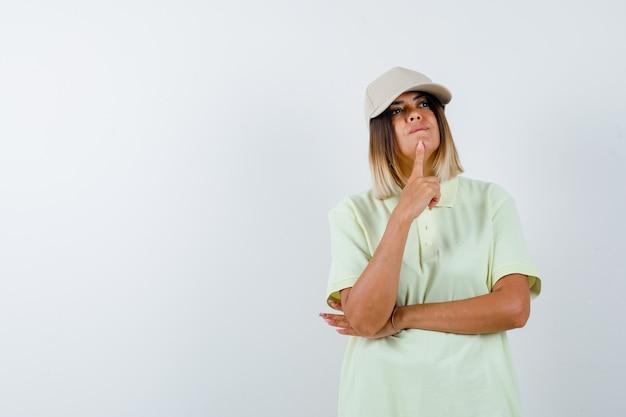 Ortrait di giovane donna in piedi nel pensare pongono in t-shirt, berretto e guardando premurosa vista frontale