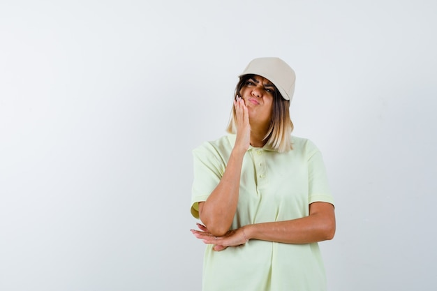 Ortrait of young lady suffering from toothache in t-shirt, cap and looking unwell front view