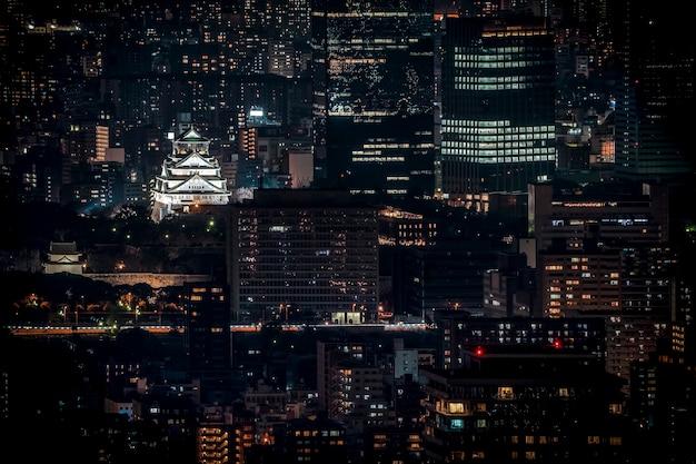 Замок осаки, освещенный ночью под взором птицы или сверху, с городским пейзажем и высоким зданием вокруг, префектура осака, япония.
