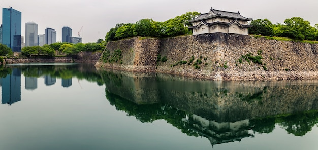 Osaka castle walls and modern office buildings with reflections in moat
