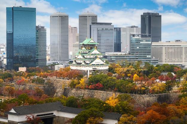 Osaka castle with japanese garden and city office building skyscraper at autumn season in osaka, japan.