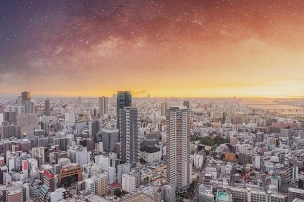 夜明けの星空と日の出の大阪の街並