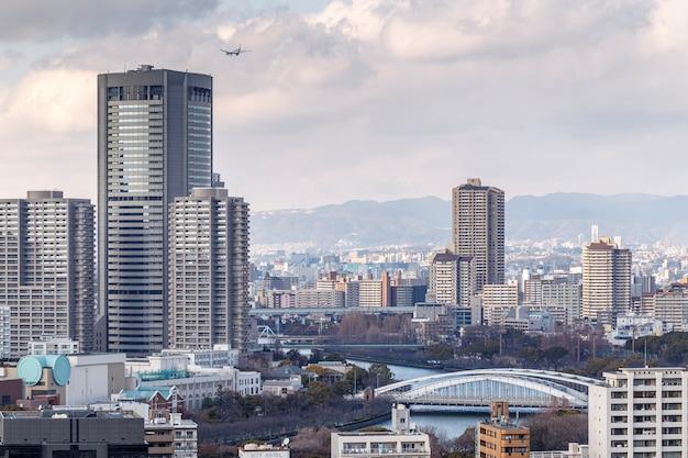 오사카, 일본-2014 년 2 월 21 일 : 오사카 성에서 촬영 한 백그라운드에서 산이있는 오사카의 풍경.