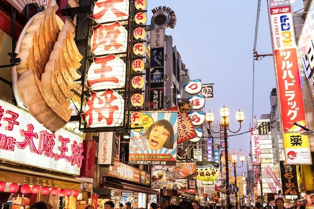 Осака, япония - 14 июня 2017: городской пейзаж осаки ночью, полный ярких рекламных щитов. район дотонбори является одним из туристических центров с множеством ресторанов, магазинов и развлекательных заведений.