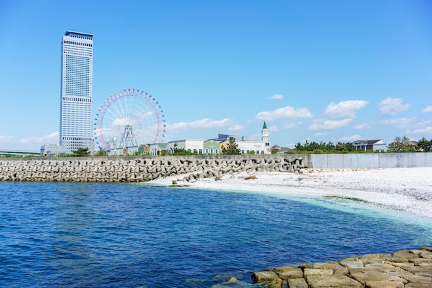 Osaka , japan - may 10 , 2018 : artificial white marble beach along the shoreline of rinku town viewing rinku gate tower building and ferris wheel