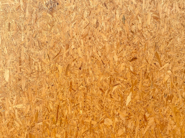 Предпосылка стены текстуры древесины osb коричневая.