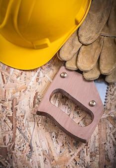 Защитные кожаные перчатки строят шлем ручной пилой на osb