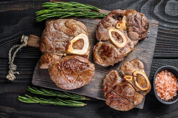 Osso buco는 송아지 고기 스테이크, 이탈리아 ossobuco를 요리했습니다. 검은 나무 배경. 평면도.