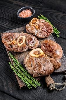 Osso buco 요리 송아지 고기 생크 스테이크, 이탈리아 ossobuco. 검은 나무 배경. 평면도.