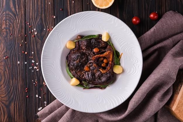 オッソブーコ-牛肉のシャンクの根菜、ハーブ、ワインとミニポテトの煮込み