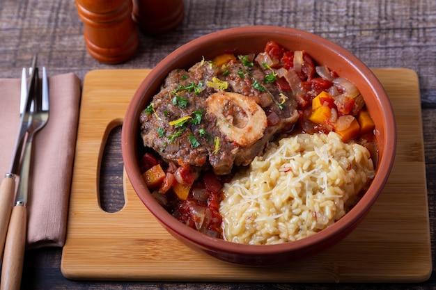 오소부코. 밀라네즈, 그레몰라타, 소스를 곁들인 사프란 리조또를 곁들인 송아지 고기(쇠고기) 정강이. 전통적인 이탈리아 요리입니다. 확대. 프리미엄 사진