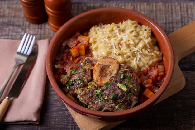 Оссобуко. голени телятины с ризотто с шафраном в миланском соусе, гремолате и соусе. традиционное итальянское блюдо.