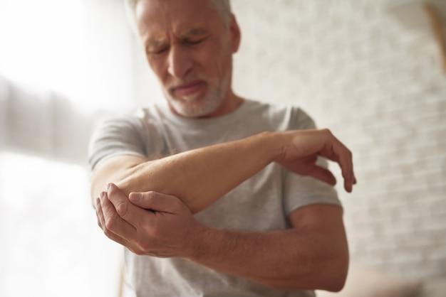 Osteoarthritis unwell senior man holding arm.