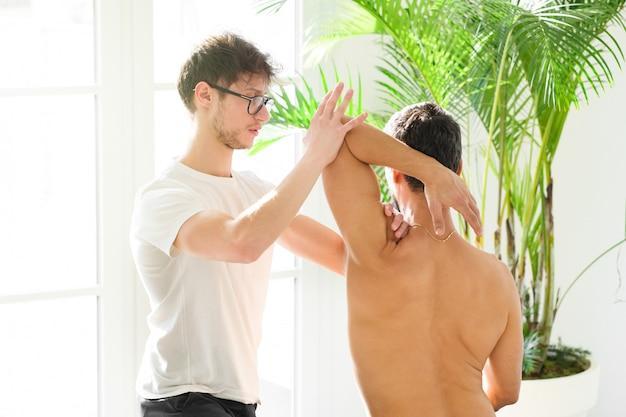 Остеопат делает оценку плеча на человека