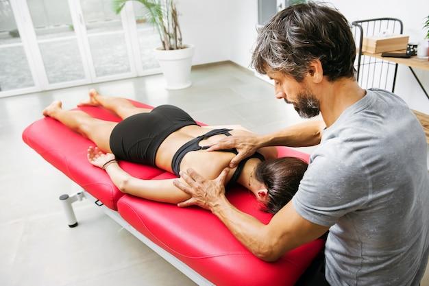 건강 또는 의료 개념에서 건염을 완화하기 위해 힘줄을 마사지하는 젊은 여성 환자에게 supraspinatus 근막 마사지를하는 정골