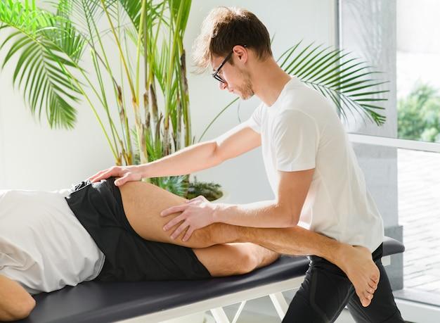 Osteopath doing a tensor fasciae latae treatment