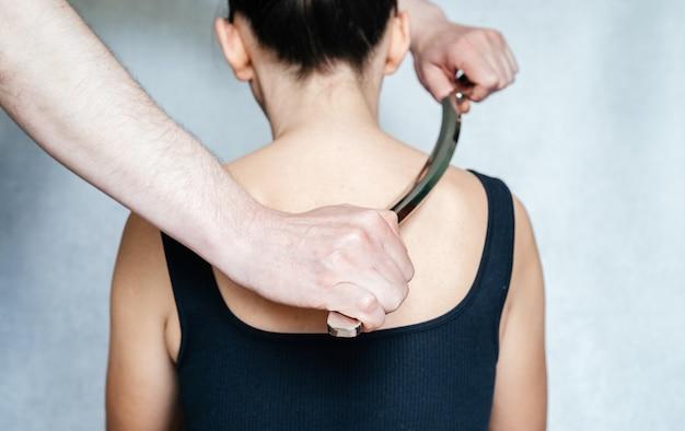 Врач-остеопат, выполняющий манипуляции по высвобождению фасции с использованием процедуры iastm, женщина получает лечение мягких тканей шеи с помощью инструмента из нержавеющей стали.