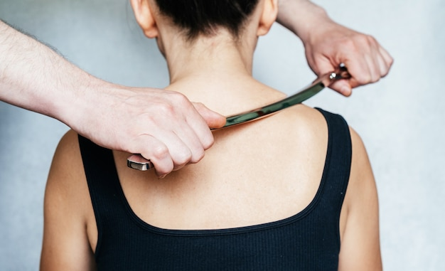 Osteopath practitioner performing fascia release maniupulations using iastm treatment a woman receiv...