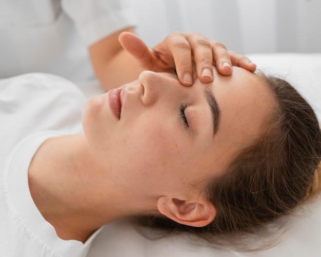 Остеопат лечит пациентку, массируя ее лицо крупным планом