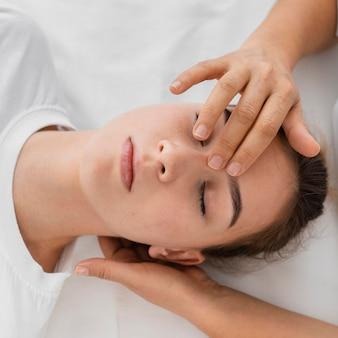 Остеопат лечит пациента, массируя ее лицо
