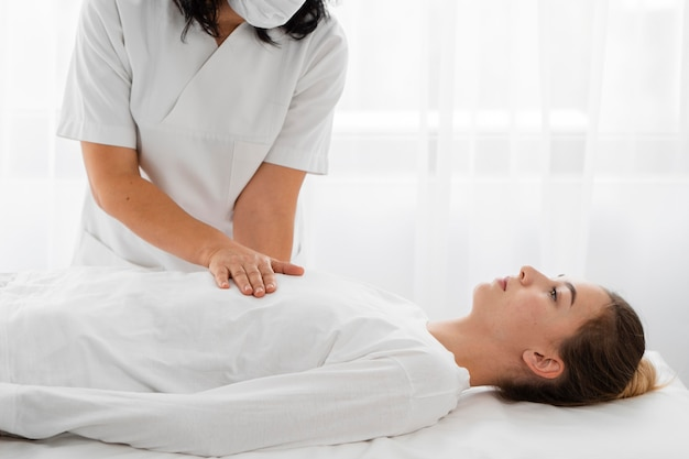Osteopathist treating a female patient by massaging her body