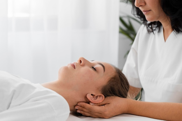 Osteopathist treating a female patient by massaging her face