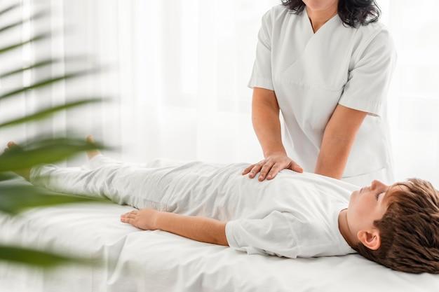 Osteopata che cura un bambino massaggiandolo in ospedale