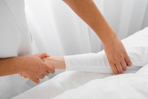 Osteopata che tratta il primo piano delle braccia di un paziente
