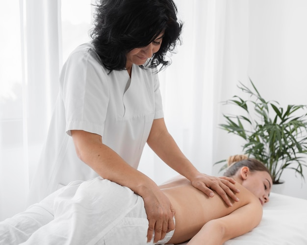 Osteopathist treating a shirtless woman at the hospital