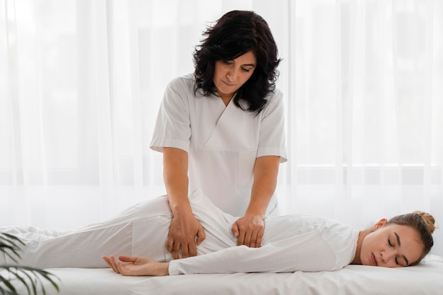 Osteopathist treating a woman indoors