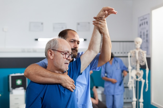 Osteopathy assistant stretching arm and shoulder of patient