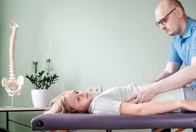 Ostheopath practitioner releasing the diaphragm of a female patient, rib cage release massage, breathing muscle relaxation