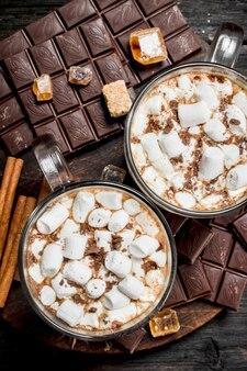 От шоколада в чашках с зефиром на деревянном столе.