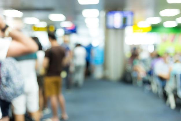 空港で荷物を持って飛行機で出発するために一緒に待っているot人の焦点をぼかす