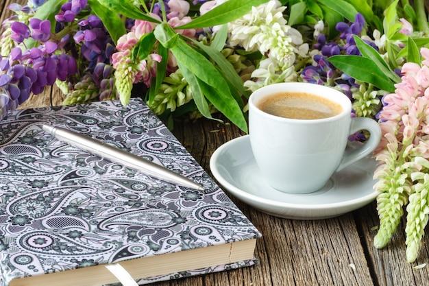 ヴィンテージの木製のテーブルの上に花とotebook