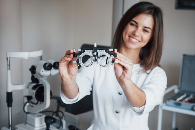 Other equipment in the room. young attractive female ophthalmologist with special device for testing eyes standing in the office.