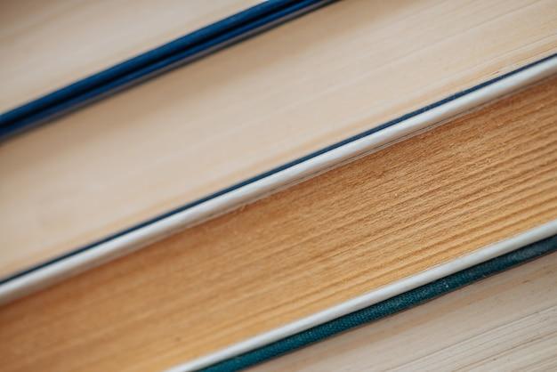 ヴィンテージ本のクローズアップ。学校の図書館で使用される古い文献のスタック。古い混oticとした読み物の背景。コピースペースで斜めにほこりだらけの本。古い本屋。