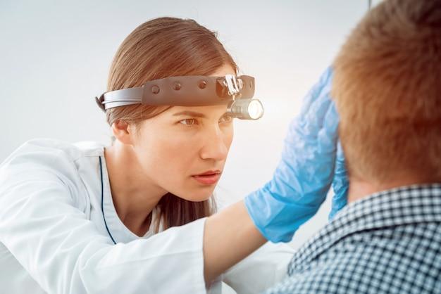 耳鼻咽喉科医は若い男の耳を調べます。