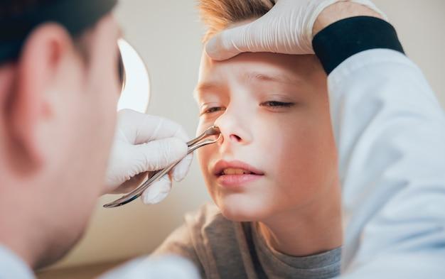 耳鼻咽喉科医は、鼻腔拡張器で少年の鼻を調べます。