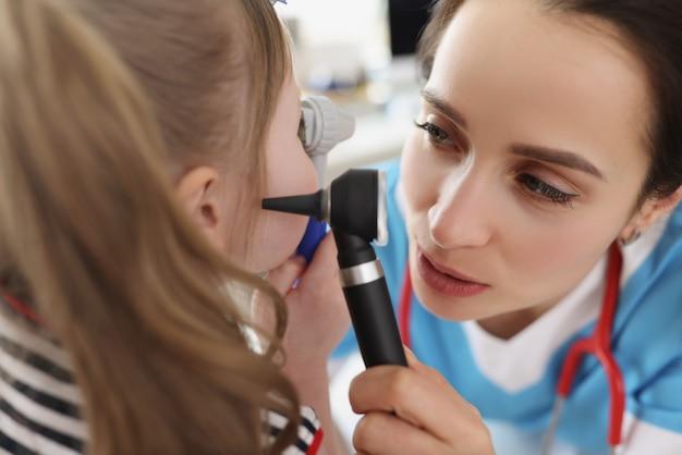 耳鼻咽喉科医が小さな女の子の患者の耳を調べます