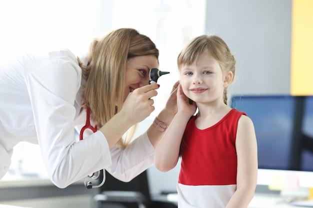 이비인후과 의사는 어린 소녀의 귀를 검사합니다.