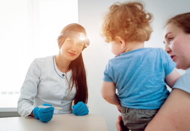 耳鼻咽喉科医は小さな男の子を調べます。