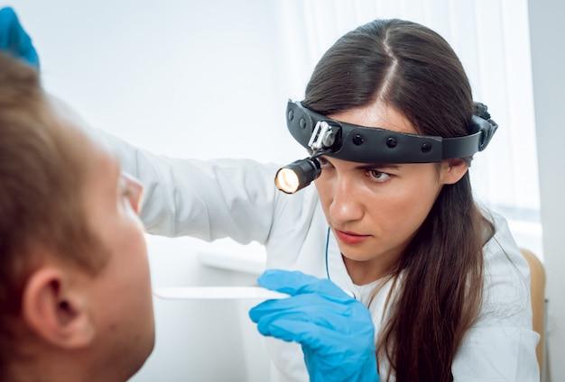 耳鼻咽喉科医は、ヘラで男性の喉を検査します。