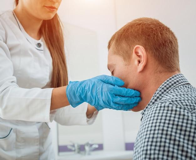 耳鼻咽喉科医が男性の喉を検査します。