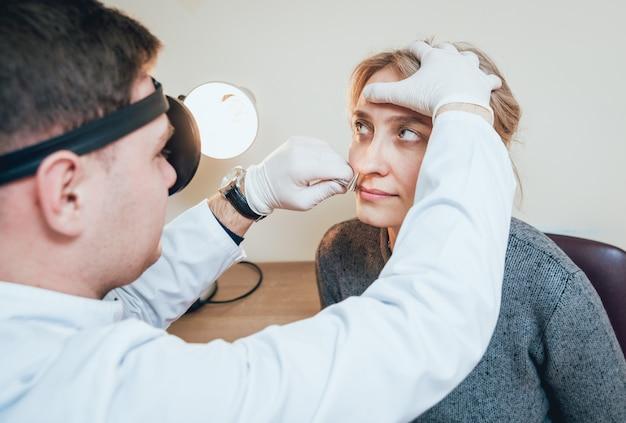 Отоларинголог осматривает нос женщины с помощью расширителя носа.
