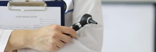 耳鼻咽喉科医は耳鏡を手に持っています。