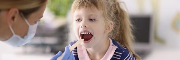 木製の少女の喉を調べる保護医療マスクの耳鼻咽喉科医..。