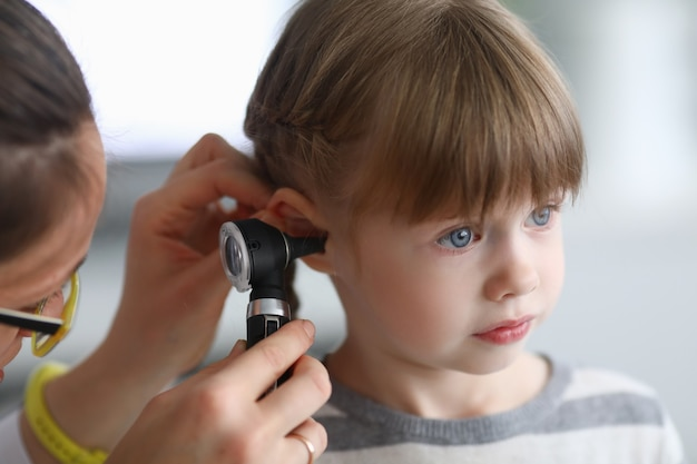 Otorhinolaryngologist examines little girl's ear with otoscope. adenoiditis as cause of otitis media in children concept.