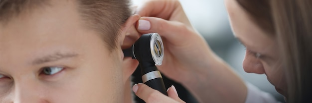 耳鼻咽喉科医が耳鏡のクローズアップで病人の耳を調べる