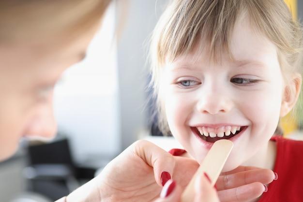 주걱으로 작은 아이의 목구멍을 검사하는 이비인후과. 어린이 개념의 편도선염 진단 및 치료